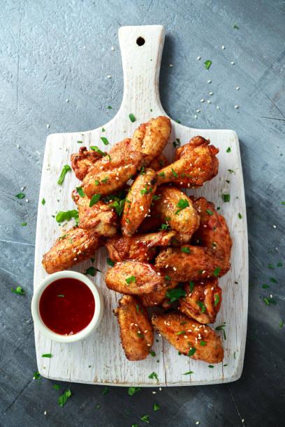 gebackene hühnerflügel mit sesam und süßer chilisauce auf weißen holzbrett. - gewürz für gegrilltes hähnchen stock-fotos und bilder