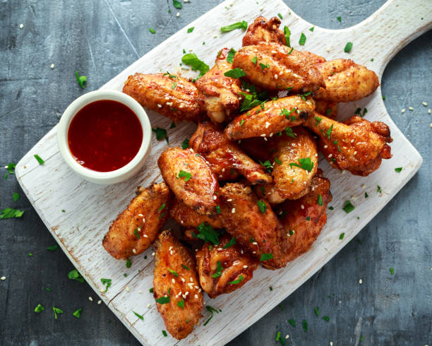 baked chicken wings with sesame seeds and sweet chili sauce on white wooden board. - ala di animale foto e immagini stock