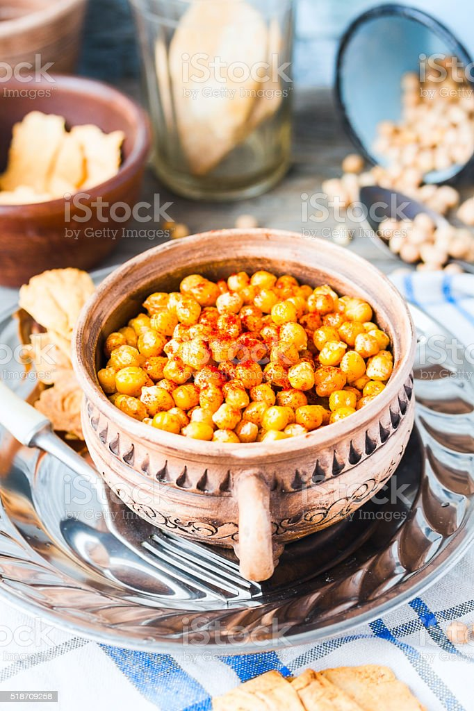 baked chickpeas with spices on rustic background, smoked paprika stock photo