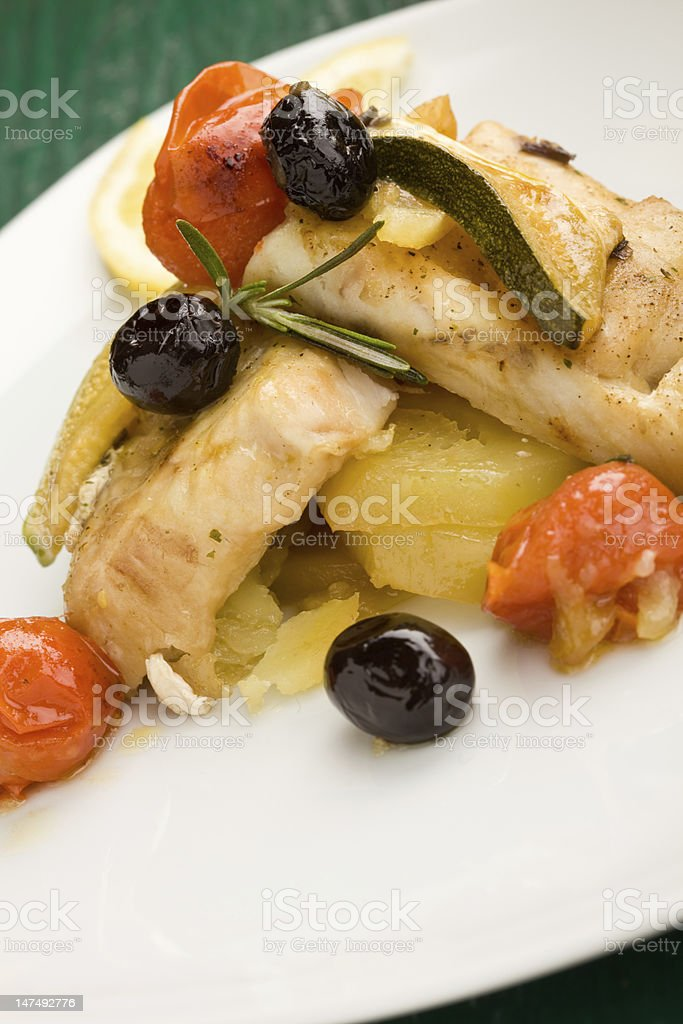 Baked Cod with olives and tomatoes stock photo