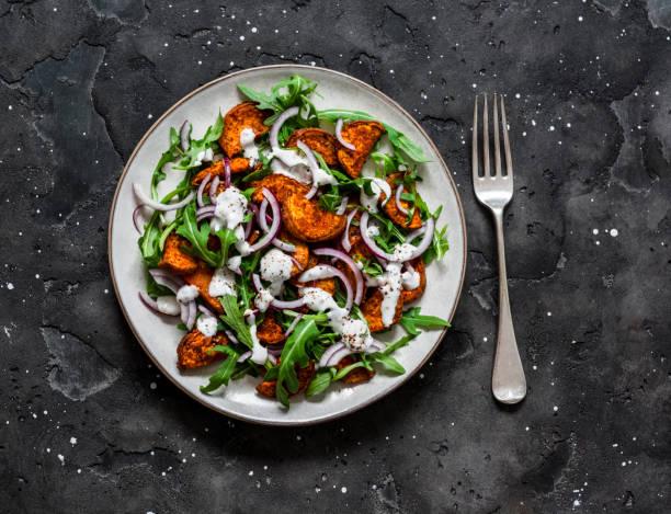 Gebackene knusprige Süßkartoffeln, Rucola, rote Zwiebel und Joghurt Senf Dressing Salat auf dunklem Hintergrund, Ansicht von oben – Foto
