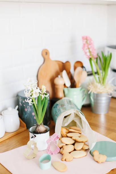 Gebackene Osterkekse in Metallbehälter auf Holztisch in der Küche – Foto