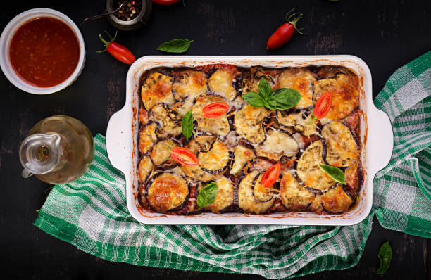 Baked eggplant with cheese on a dark wooden table. Parmigiana melanzane. Top view. Italian cuisine. Copy space stock photo