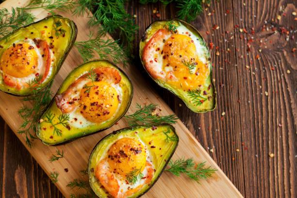 Baked eggs in avocado with smoked salmon stock photo