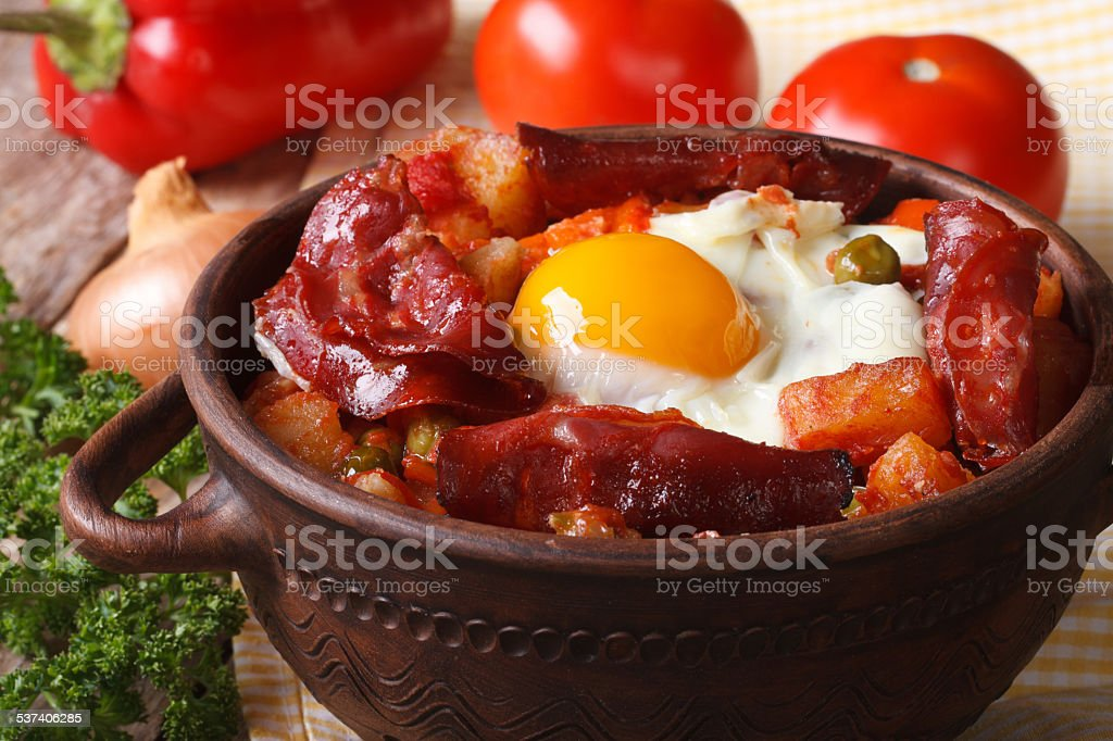 Baked eggs with chorizo and vegetables in the pot. Horizontal stock photo