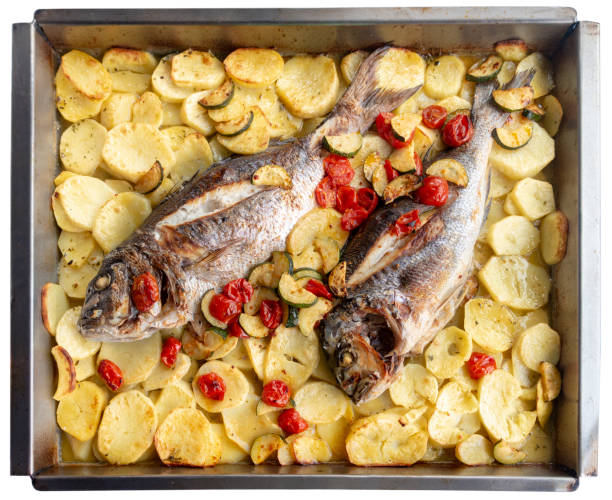 baked fish and potatoes from the oven, from above, on white background - peixe na grelha imagens e fotografias de stock