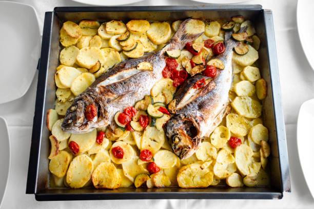baked fish and potatoes from the oven - peixe na grelha imagens e fotografias de stock