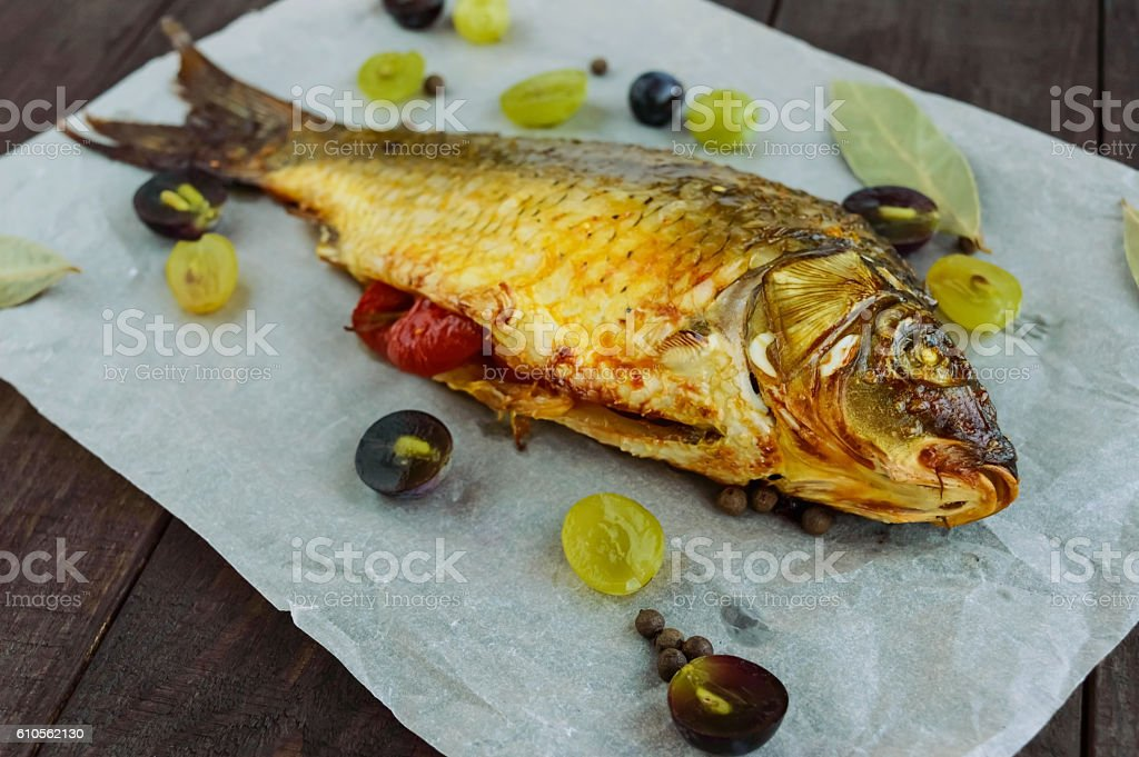 Baked fish carp, stuffed bell peppers and grapes. stock photo