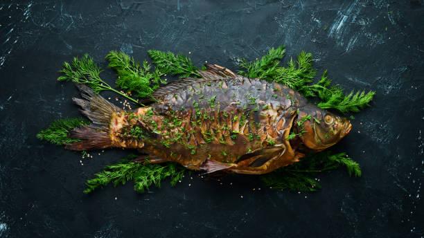 Carpa cozida dos peixes com vegetais. Vista superior. Espaço livre para o seu texto. Estilo rústico. - foto de acervo