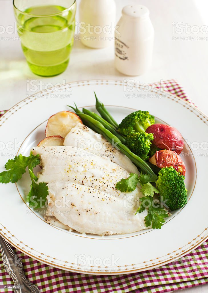 Baked fish fillet served with broccoli, green bean and potato stock photo