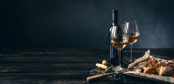 baked fish dinner concept for two. two glasses of white wine, baked fish. fine dining stock pictures, royalty-free photos & images