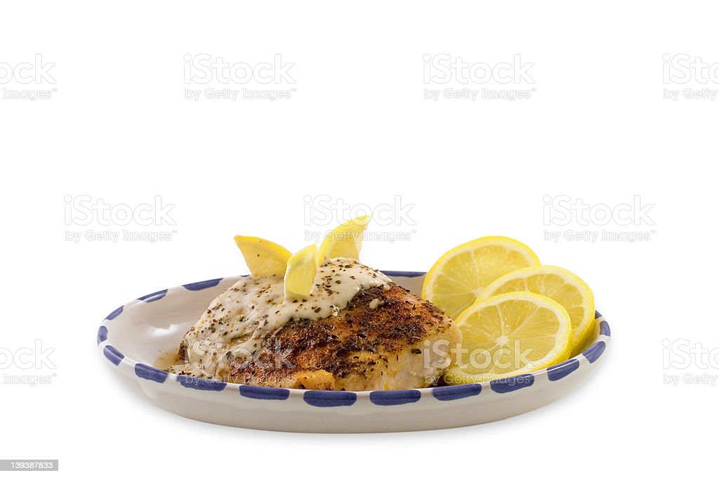 Baked Fish with Lemon Slices & Sauce royalty-free stock photo