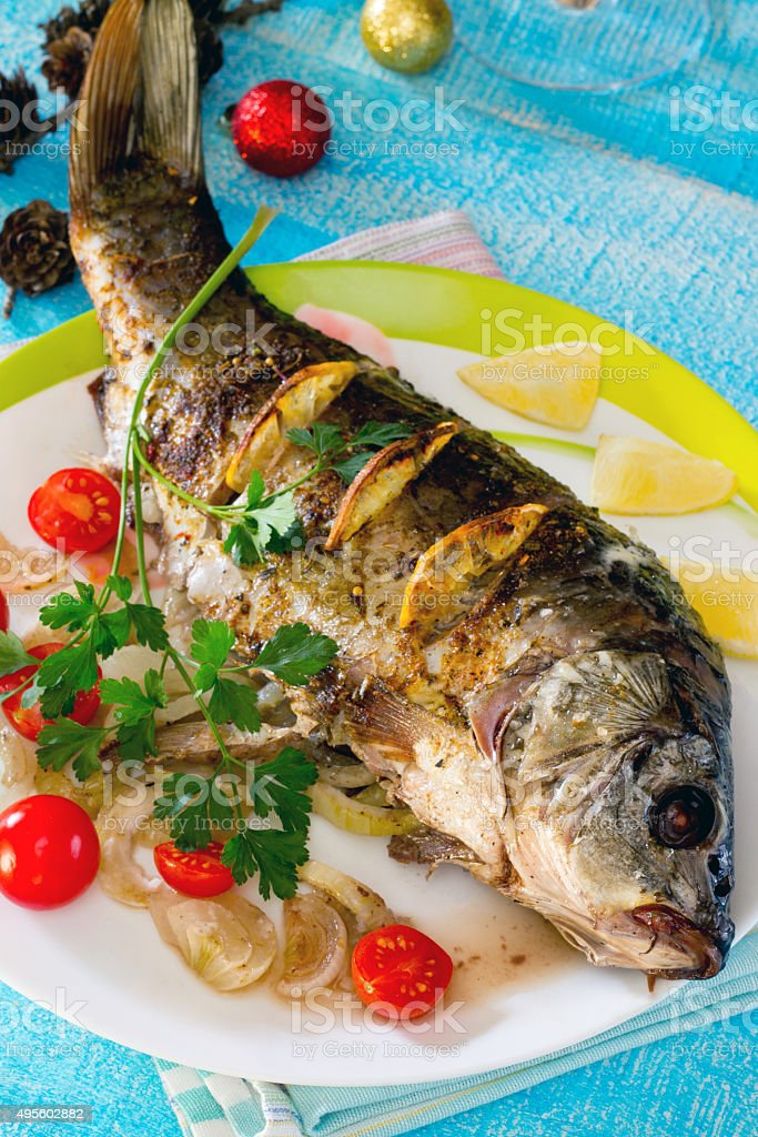 Baked fish (carp) with onion and lemon stock photo