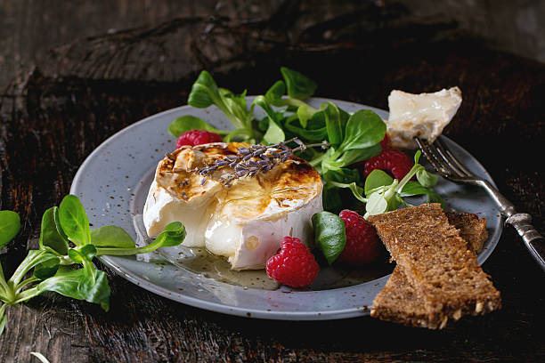 baked goat cheese with honey and raspberries - baked brie stock photos and pictures