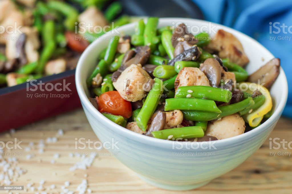 Baked green beans, chicken meat, cherry tomatoes, mushrooms, lemon, sesame stock photo