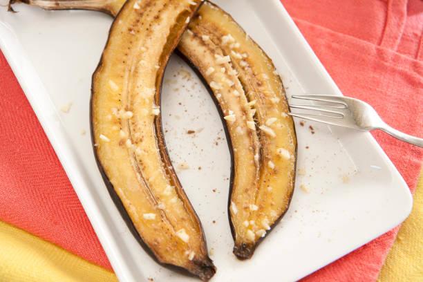 gegrillte banane hälften mit honig und nüssen gebacken. - gebackene banane stock-fotos und bilder
