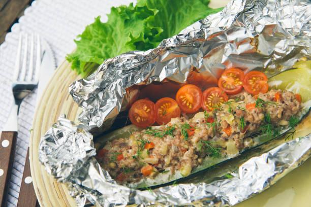 in folie gehacktem hühnerfleisch gefüllte zucchini mit gemüse gebacken. diät-rezept. - alufolie backofen stock-fotos und bilder