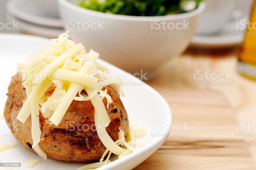 Baked jacket potato with butter and grated cheddar cheese royalty-free stock photo