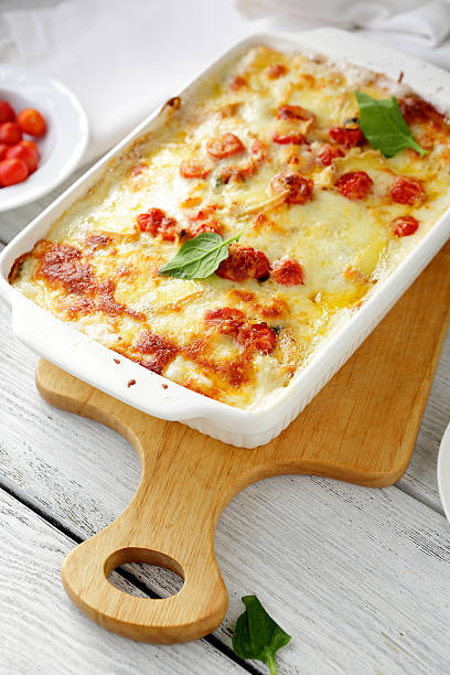 baked lasagna in white dish stock photo
