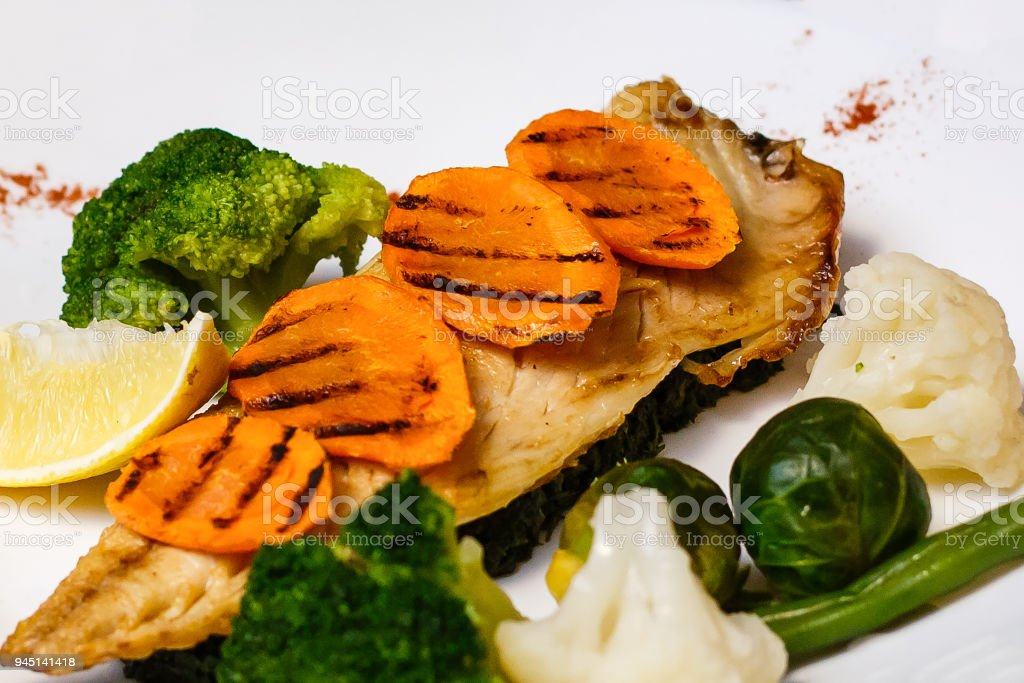Baked mackerel fish stuffed with carrots. Top flat view. Close-up.