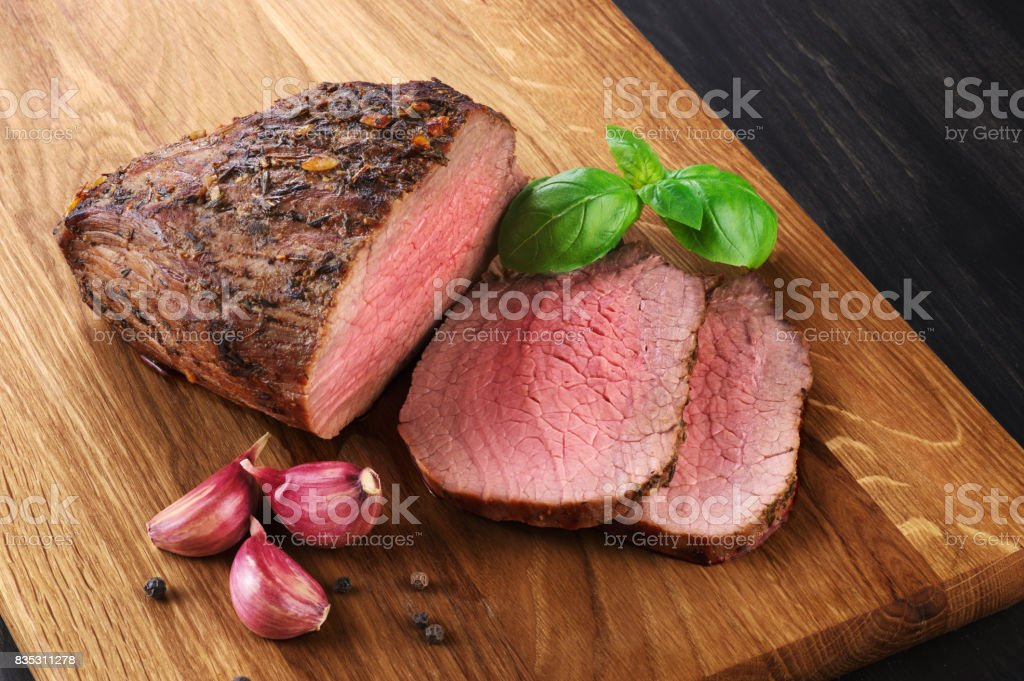 Baked meat, garlic and basil on a wooden background. Roast beef. stock photo