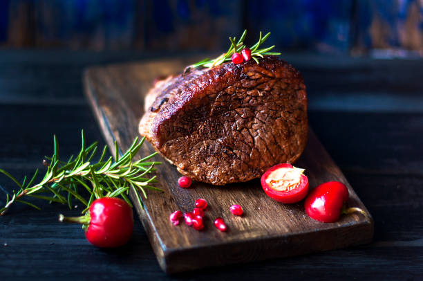 baked meat with rosemary and red pepper. steak. beef. dinner for men. dark photo. Black background. wooden board. baked meat with rosemary and red pepper. steak. beef. dinner for men. dark photo. Black background. wooden board main course stock pictures, royalty-free photos & images
