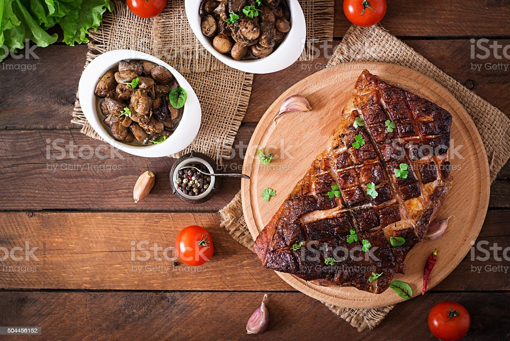 Baked meat with spices and garlic on wooden table. stock photo
