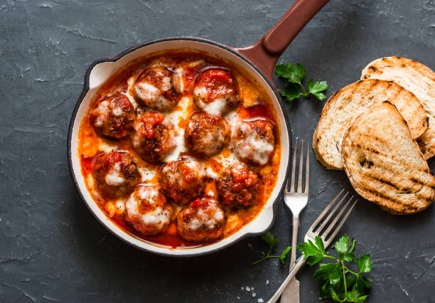 Baked meatballs with mozzarella and tomato sauce in a cast iron skillet on a dark background, top view Baked meatballs with mozzarella and tomato sauce in a cast iron skillet on a dark background, top view meatball stock pictures, royalty-free photos & images