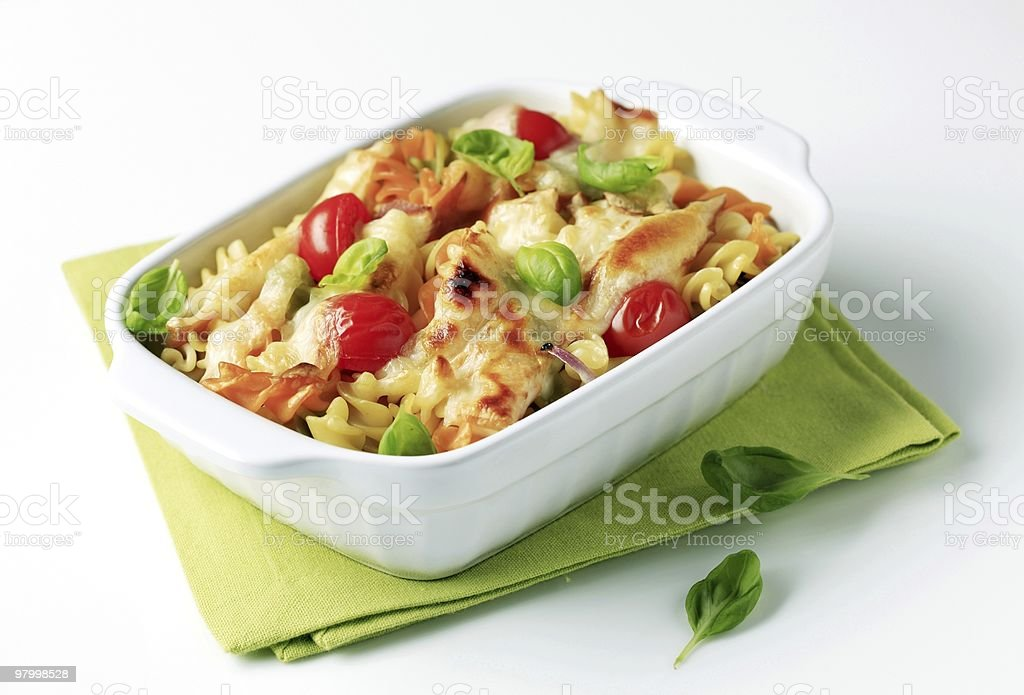 Baked pasta dish adorned with red tomatoes and veggies stock photo