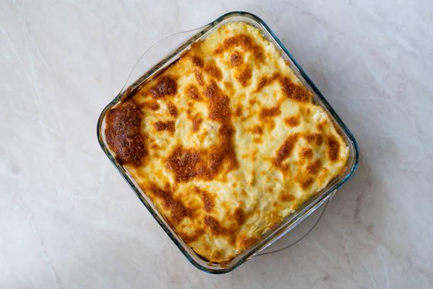 Macarrão assado com molho de queijo Bechamel e espinafre / Ziti Bolognese em Tigela de Vidro. - foto de acervo