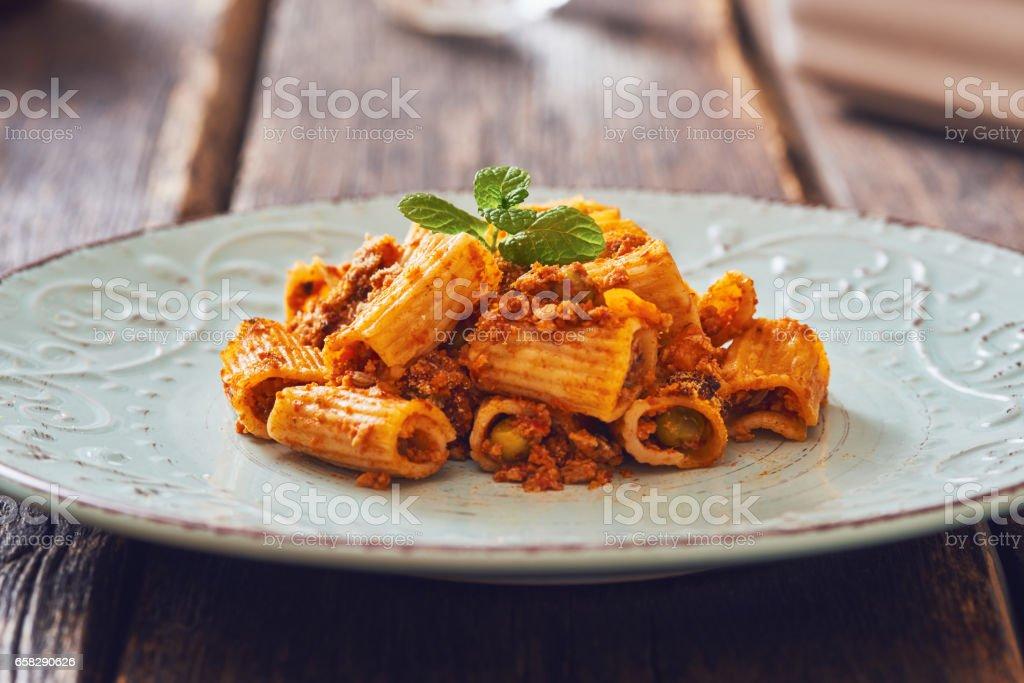 Baked pasta with ragu' sauce on vintage plate. stock photo