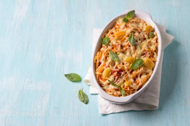 Gebackene Nudeln mit Tomatensoße, Knoblauch, Käse und Basilikum – Foto