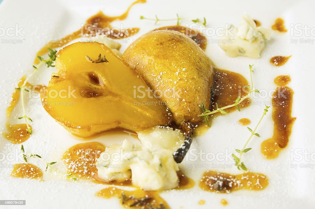 baked pear with caramel and gorgonzola cheese stock photo