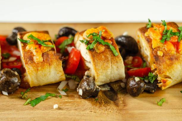Pedaços assados de tortilla embrulho com peito de frango e queijo Grana Padano na madeira - foto de acervo