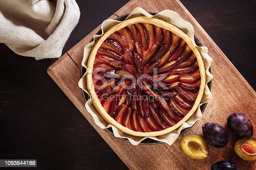 istock Baked plum pie on a pan of fresh plums 1093644188