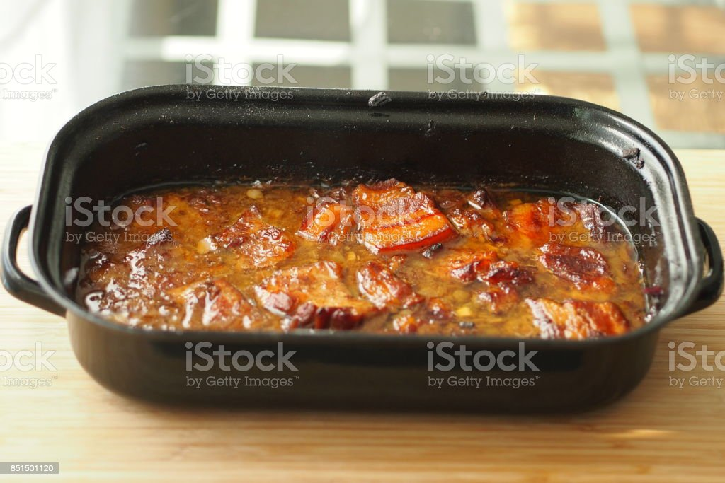 Baked pork belly with a sauce in a black roasting pan on a wooden table. Traditional specialty form the Czech Republic called 'moravsky vrabec'. stock photo