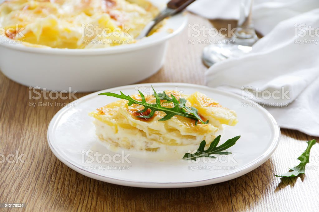 Baked potato Dauphinois on a plate. stock photo