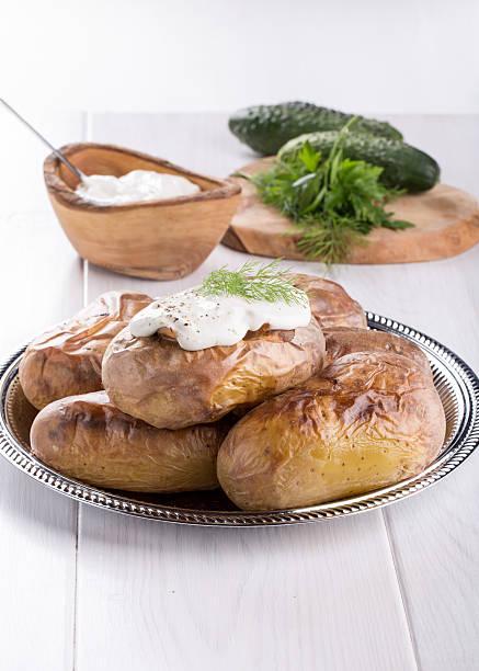 baked potato topped with sour cream sauce - ofengemüse mit feta stock-fotos und bilder