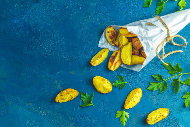 Baked potato wedges on paper with addition sea salt and parsley stock photo
