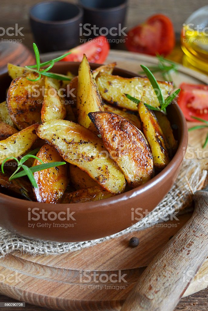 Baked potato wedges with rosemary and garlic Стоковые фото Стоковая фотография