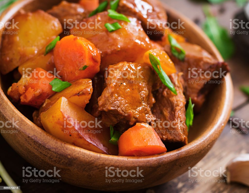 Baked potato with beef Bourguignon on the old wooden background in rustic style. Flat lay. Top view stock photo