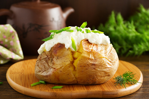 istock Baked potato with cream of the cream cheese closeup. 524091379