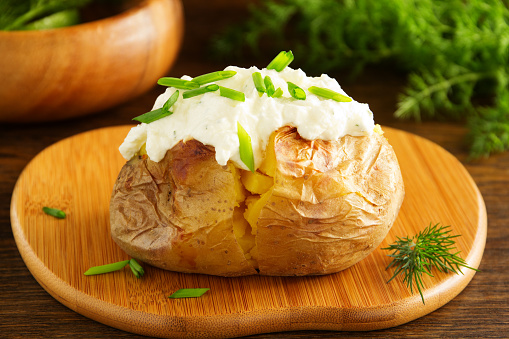 istock Baked potato with cream of the cream cheese closeup. 525675605
