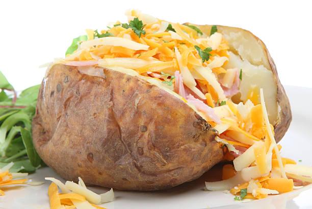 Batata assada com queijo e presunto & - foto de acervo