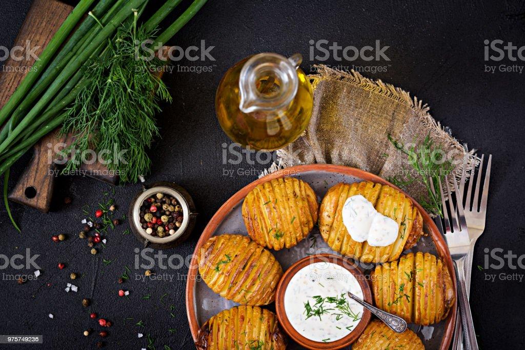 Ofenkartoffel mit Kräutern und Soße auf schwarzem Hintergrund. Veganes Essen. Gesunde Mahlzeit. Ansicht von oben. Flach zu legen - Lizenzfrei Asiatisch Stock-Foto
