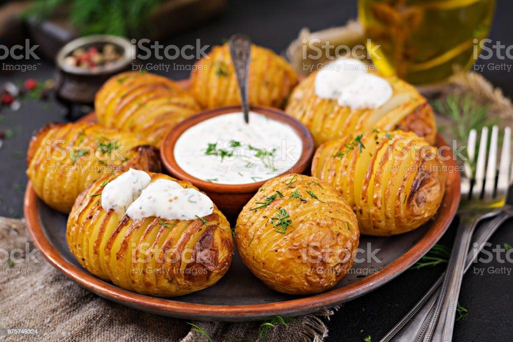 Ofenkartoffel mit Kräutern und Soße auf schwarzem Hintergrund. Veganes Essen. Gesunde Mahlzeit. - Lizenzfrei Asiatisch Stock-Foto