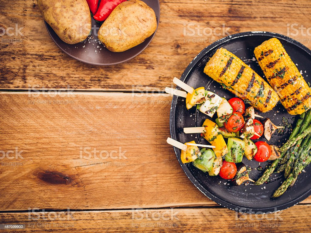 Baked potatoes and grilled vegetables on a vintage wooden table stock photo