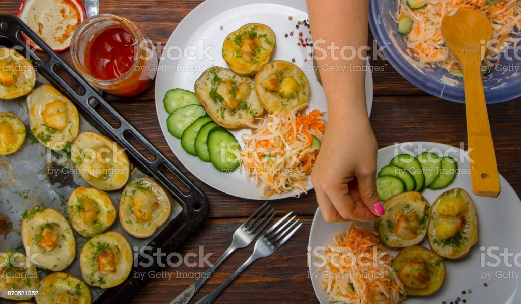 baked potatoes in a baking sheet on a wooden table top view stock photo