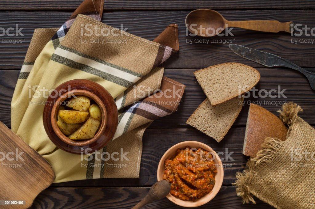 Baked potatoes in a clay pot, bread and sauce on a wooden table royalty-free stock photo