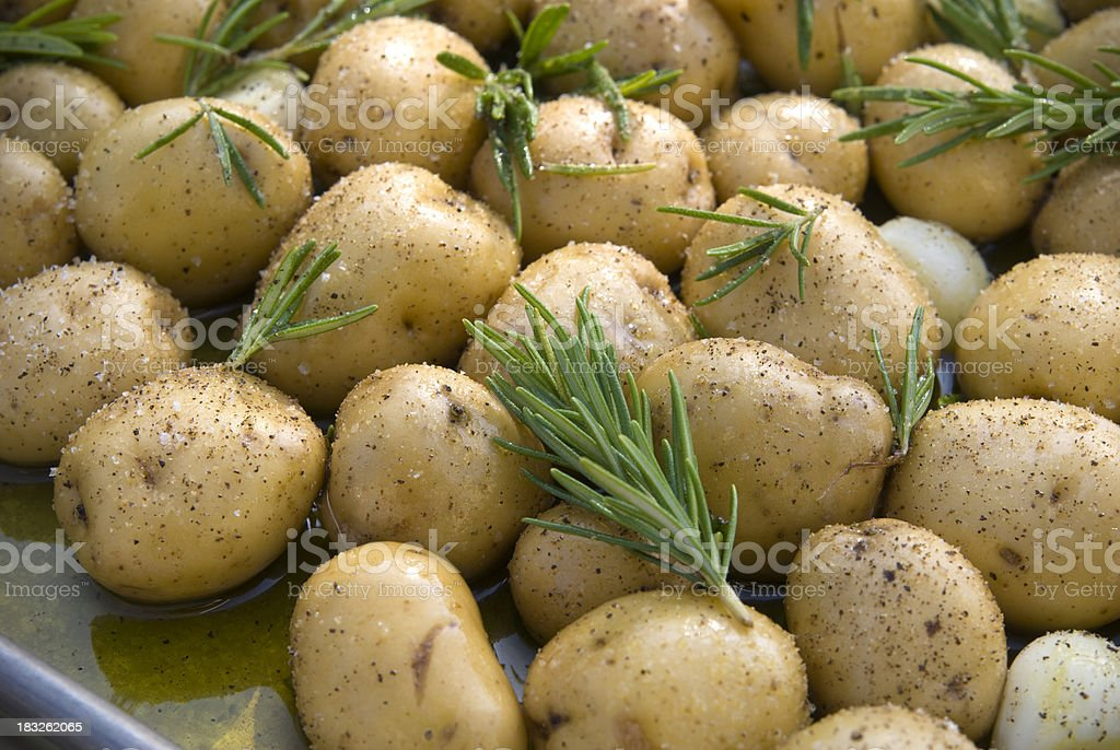 Baked Potatoes in Pan, Cooking with Garlic & Fresh Rosemary stock photo